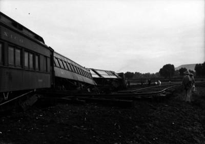 Gente observando el descarrilamiento de un tren de pasajeros
