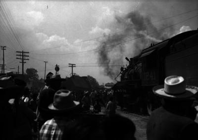 Gente y ferrocarrileros observando el choque de un ferrocarril y una locomotora