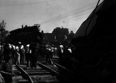 Gente levantando los escombros del choque entre una locomotora y vagones de otro ferrocarril