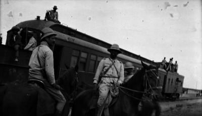 Guillermo Rubio Navarrete y un militar, ambos a caballo junto a un tren
