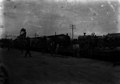 Personas en los patios de carga junto a un ferrocarril que transporta automóviles