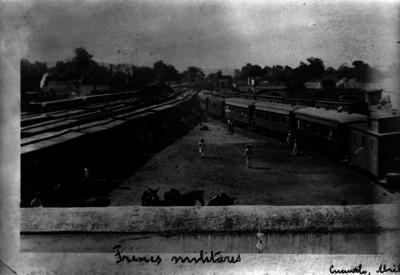 Trenes militares en patios de una estación ferroviaria, vista panorámica