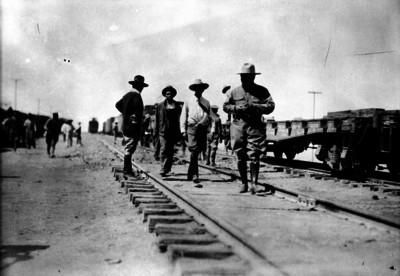 Miembros del ejército constitucionalista caminan por las vias férreas de una estación