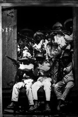 Adolescentes y niños revolucionarios con rifles desde un vagón de carga