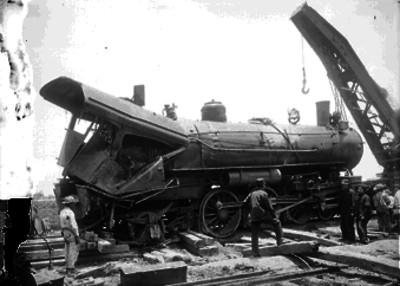 Ferrocarrileros observando los restos de una locomotora volada, en el momento de ser levantada por una grua