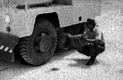 Ferrocarrilero revisando la llanta de un armón en los patios de una estación de ferrocarril