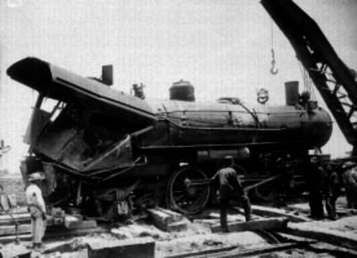 Ferrocarrileros junto a una locomotora accidentada