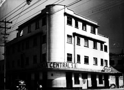 """Gente camina frente al edificio de """"Agencia Central S.A."""""""