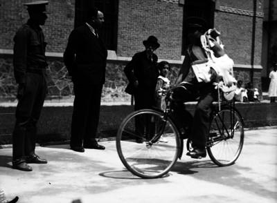 Cartero en bicicleta por la calle, vida cotidiana