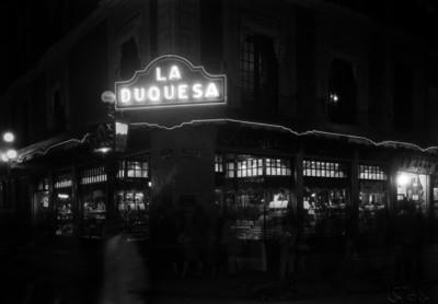 """Gente frente a las vitrinas de exhibición de la Joyeria """"La Princesa"""", toma nocturna"""