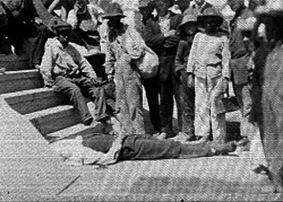 Gente observa un cadáver al pie de escalera