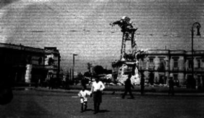 Gente observa el reloj de la Glorieta de Bucareli dañado por los combates durante la Decena Trágica