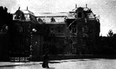 Mujer camina frente a una residencia dañada después del sitio a la Ciudadela