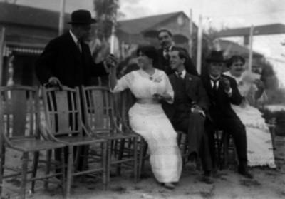 Mujer entregando objeto a un hombre durante reunión social en un jardín