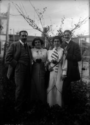 Jorge Huerta acompañado de otro hombre y dos mujeres en un jardín, retrato de grupo