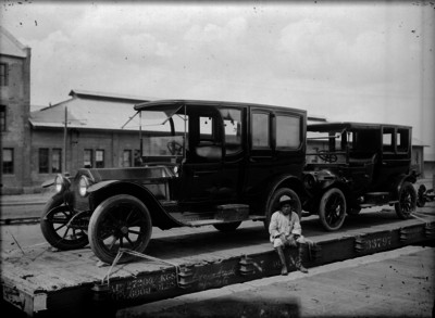 Soldado constitucionalista sentado a un costado de unos automóviles