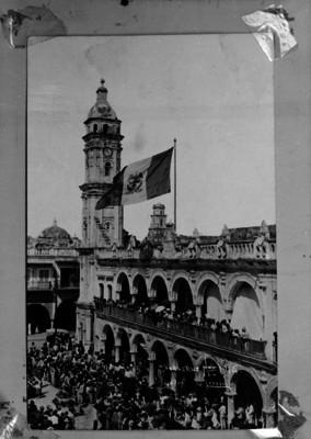 Personas observan el izamiento de la bandera en el Palacio Municipal del Puerto de Veracruz