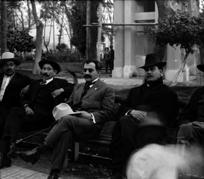 Pablo González sentado en una banca con otras personas, retrato de grupo