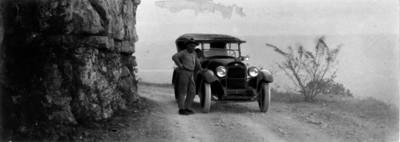 Hombre junto a automóvil estacionado en una terracería, retrato