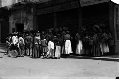 Gente en espera que abran una tienda de harina y pan, crisis de hambre en la ciudad