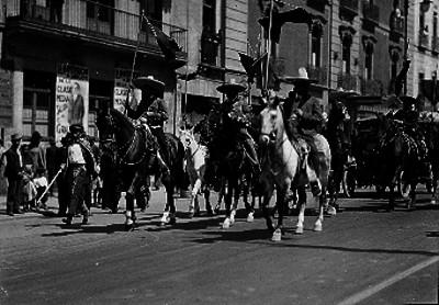 Charros montados a caballo desfilan por una calle de la ciudad
