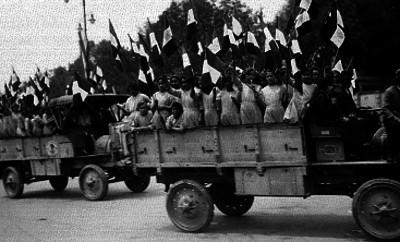 Niñas uniformadas desfilan a bordo de carros militares