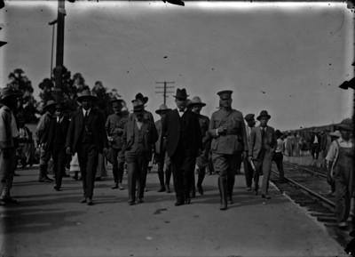 Álvaro Obregón con un grupo de funcionarios y militares camina junto a vías ferroviarias