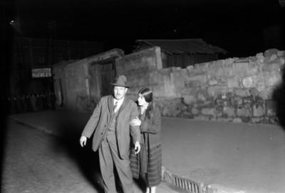 Tina Modotti acompañada por persona durante la reconstrucción del crimen de Julio A. Mella