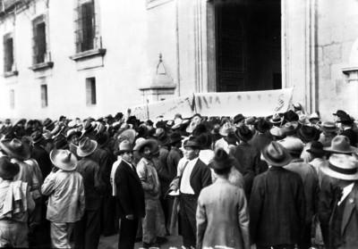Tumulto a la entrada del Palacio Nacional con pancartas aludiendo a Plutarco Elías Calles
