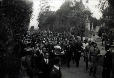 Militares y civiles trasladando una urna funeraria en un panteón