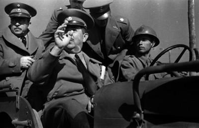 Lázaro Cárdenas con militares en un carro, conversando con un civil