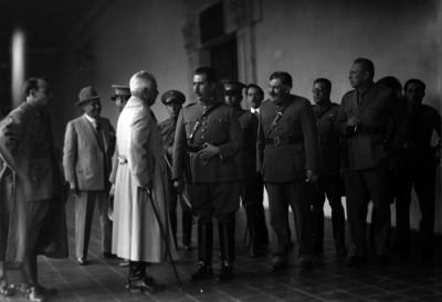 Lázaro Cárdena acompañado por militares conversando con oficial en un cuartel