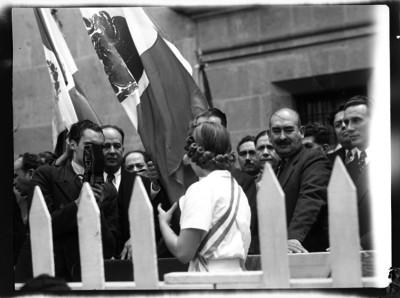 Lázaro Cárdenas abanderando a una joven en un acto público