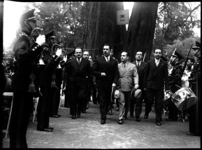 Lázaro Cárdenas acompañado de funcionarios recibiendo honores de militares