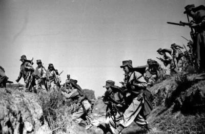 Militares saltando una trinchera durante prácticas y maniobras para la guerra