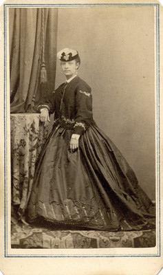 Mujer con vestido y sombrero de pie junto a una mesa