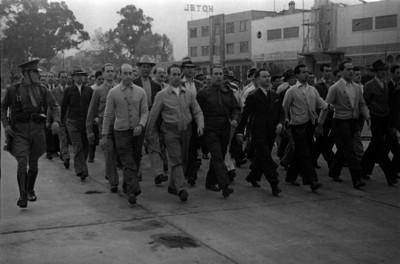 Civieles marchando dirigidos por un militar durante maniobras militares para la guerra