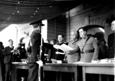 Manuel Ávila Camacho entregando documentos a militares