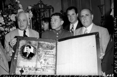 Funcionarios mostrando la solicitud para el premio de la Paz para el Miguel Alemán Valdés