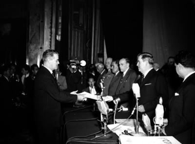 Manuel Ávila Camacho entregando reconocimiento a un hombre durante la ceremonia del 2° aniversario de alfabetización