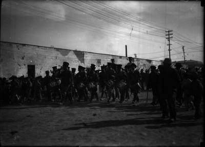 Banda de guerra militar desfila en las calles de un pueblo