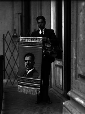 Hombre sosteniendo un sarape con la imagen de Lázaro Cárdenas