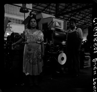 """Trabajadores frente a una máquina de la fábrica de cigarros """"El Buen Tono"""", retrato"""