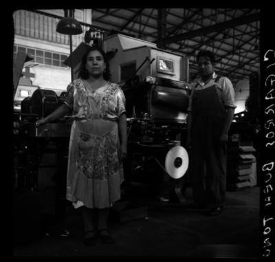 """Trabajadores frente a una máquina de la fábrica de """"cigarros El Buen Tono"""", retrato"""