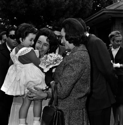 Eva Sámano de López Mateos saludando a un niño con su madre