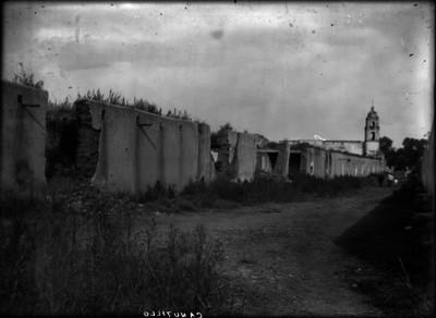 Hombres y niño caminan a un costado de la Hacienda de Canutillo