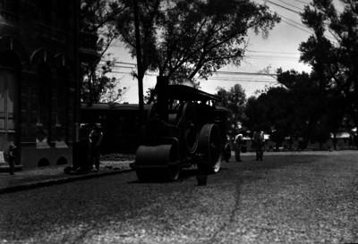 Trabajadores con aplanadora durante la reparación del pavimento en una calle