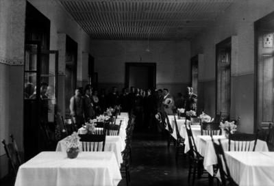 Pascual Ortíz Rubio acompañado de militares y funcionarios en el interior de un restaurante, retrato de grupo