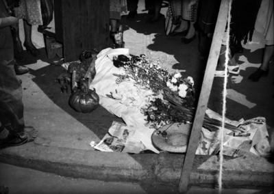 Hombre muerto siendo velado en el piso