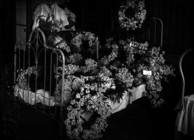 Cadáver de un niño sobre una cama rodeada de flores en una habitación